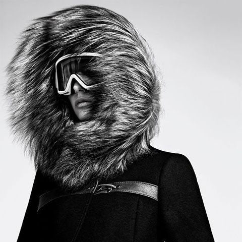 woman in ski glasses wearing a jacket with a fur hood