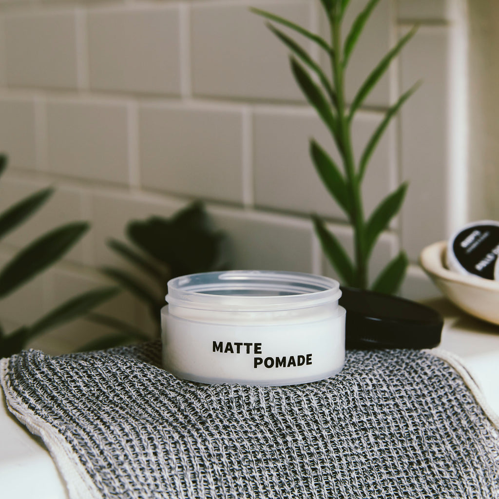 Open jar of Matte Pomade on towel on a sink with plants in the background