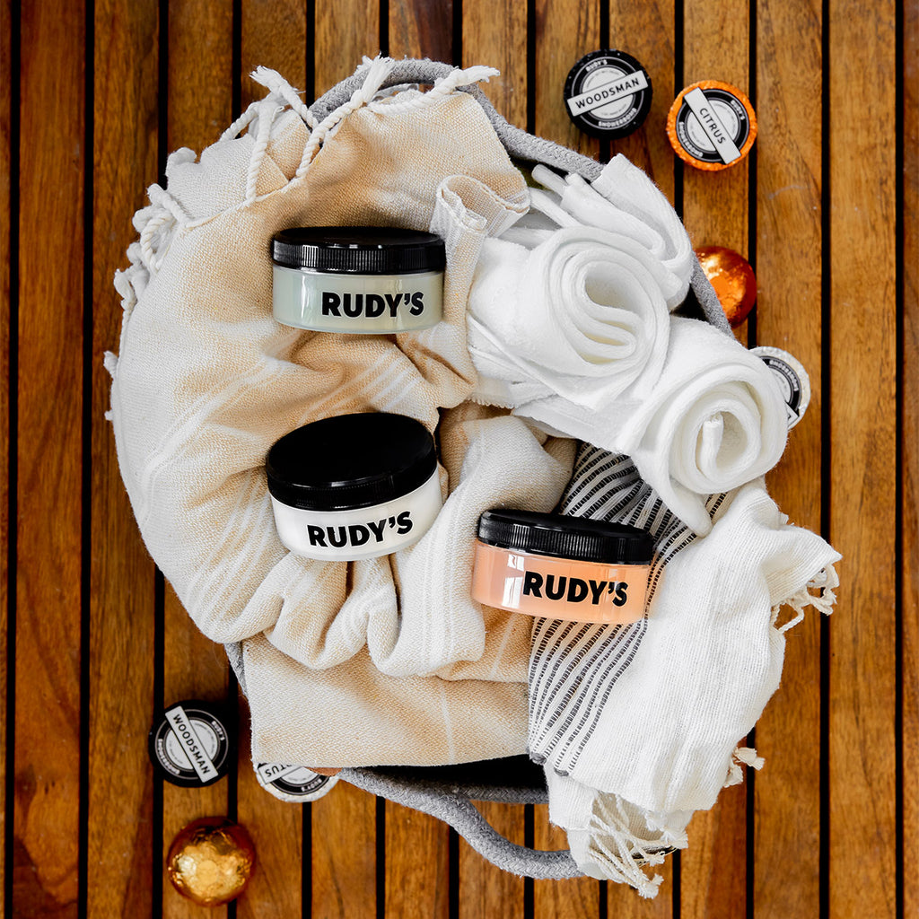 Image of Clay, Matte, and Shine Pomades in basket with towels and shower bombs
