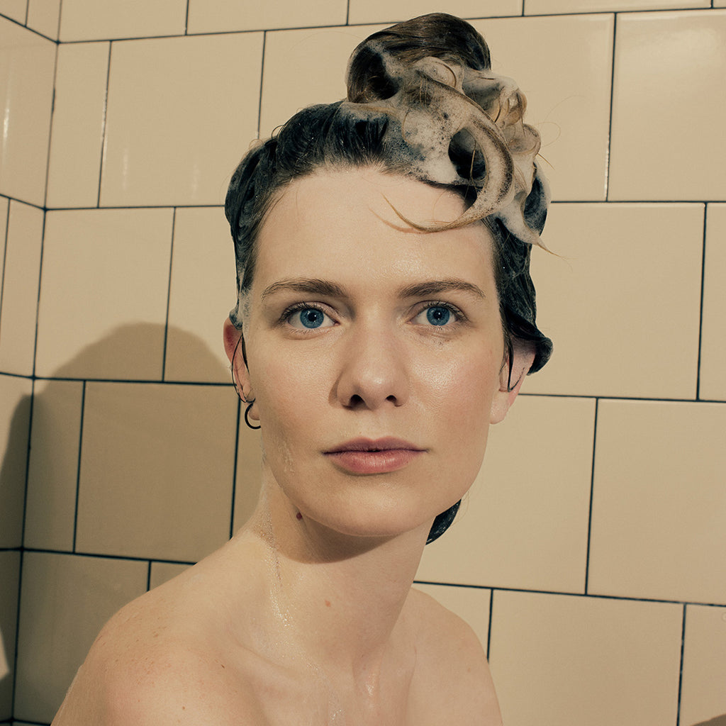 Image of a woman washing her hair with Rudy's No. 1 Shampoo