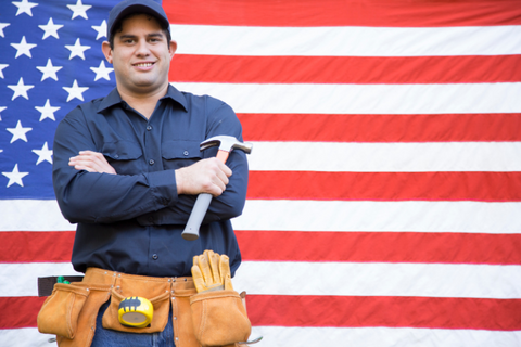 Proud working man standing in front of flag