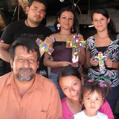 Family in El Salvador holding the handpainted Romero Crosses