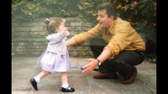 The author as a child running towards her father for a cuddle