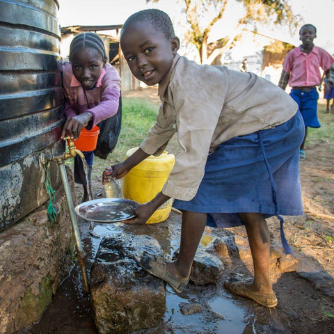 Children in Kenya collecting clean water from a water tank installed by CAFOD