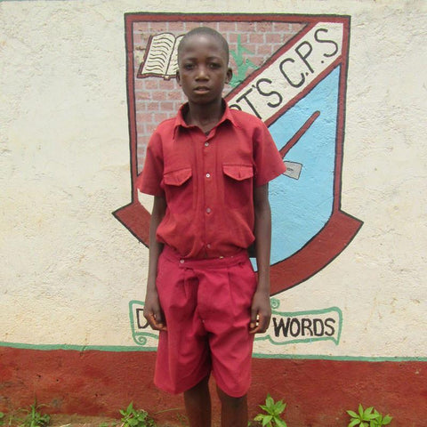 Aleck stands in front of his school. Getting a birth certificate has meant he can now get an education.