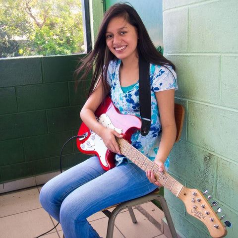 Buying the gift of play means this girl can learn the guitar in a safe place and make friends away from gangs and violence
