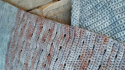 Close up of a crochet shawl made from Raxor Yarns hand-dyed yarn in greys and variegated grey and rust colours. The pattern features an eyelet section.