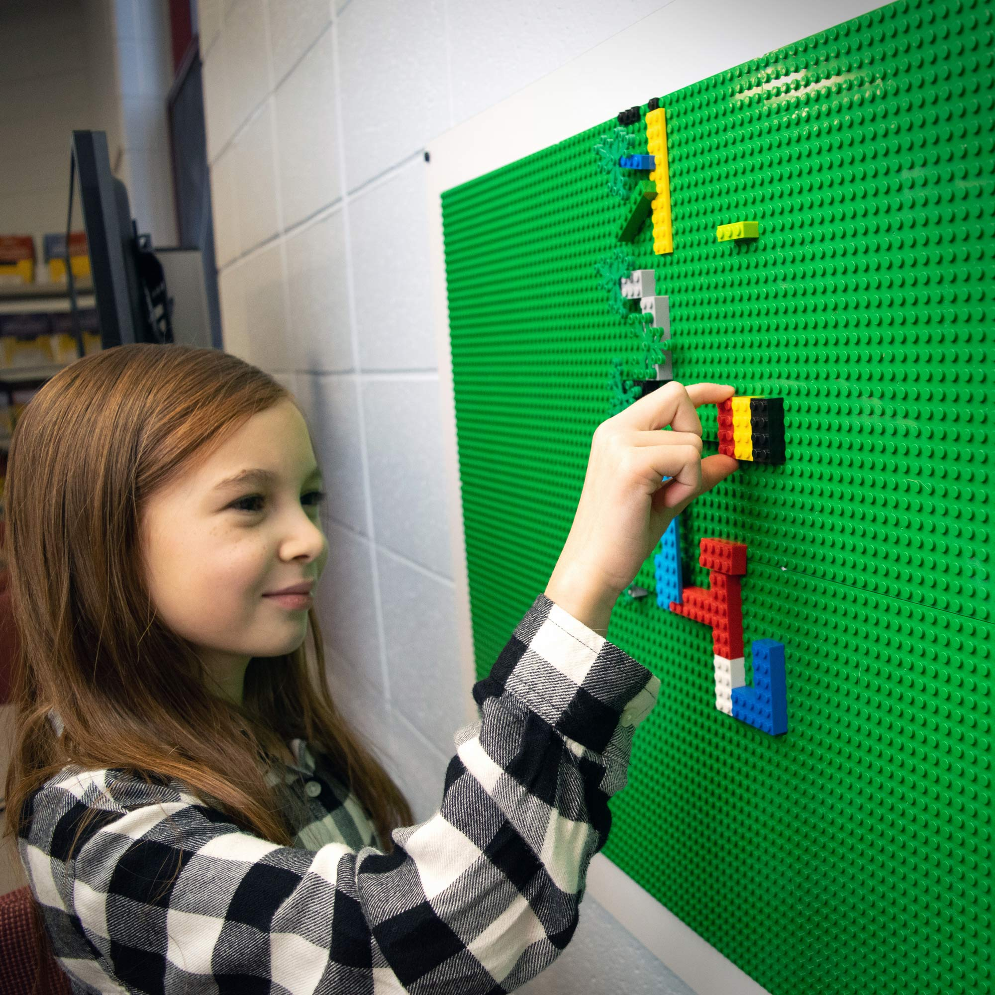 Girl playing with Lego bricks on PlayUp Wall by Creative QT