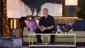 Steven Sabados sitting on a sofa with products from his Mystere Studio Collection