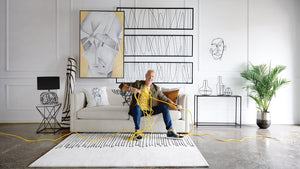 Steven Sabados sitting on a sofa while stretching a yellow cord surrounded by products from his Wired Studio collection