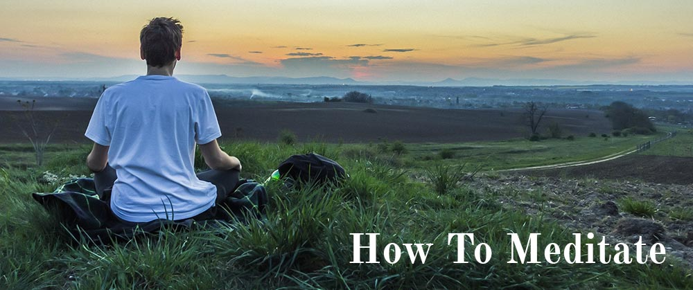 How to meditate, man sitting cross legged meditating overlooking a grassy plain during sunset