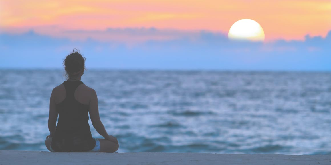 Girl meditating on a beach with the sun setting behind clouds over water during sunset