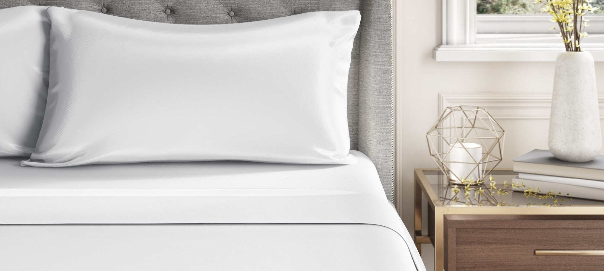 A close up of an ivory silk pillow and sheets, showing a head board and metal and wood side table