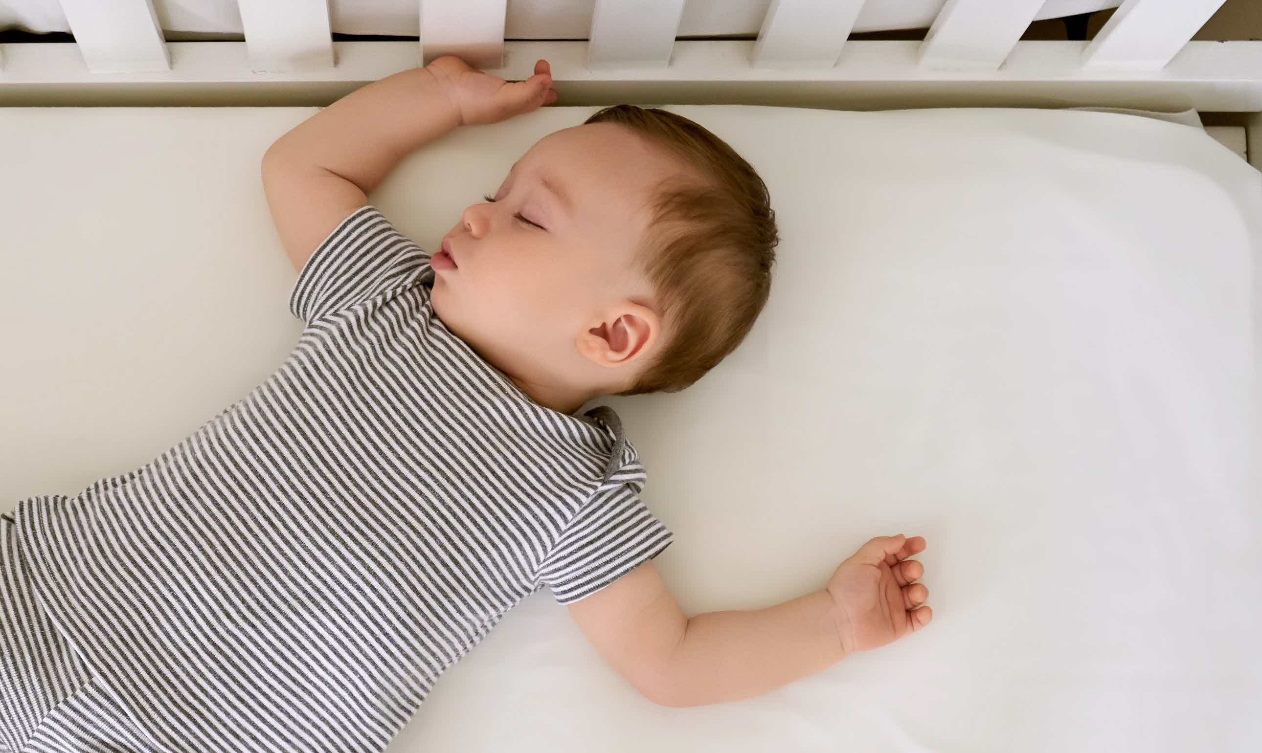 Baby boy sleeping on an ivory silk crib sheet