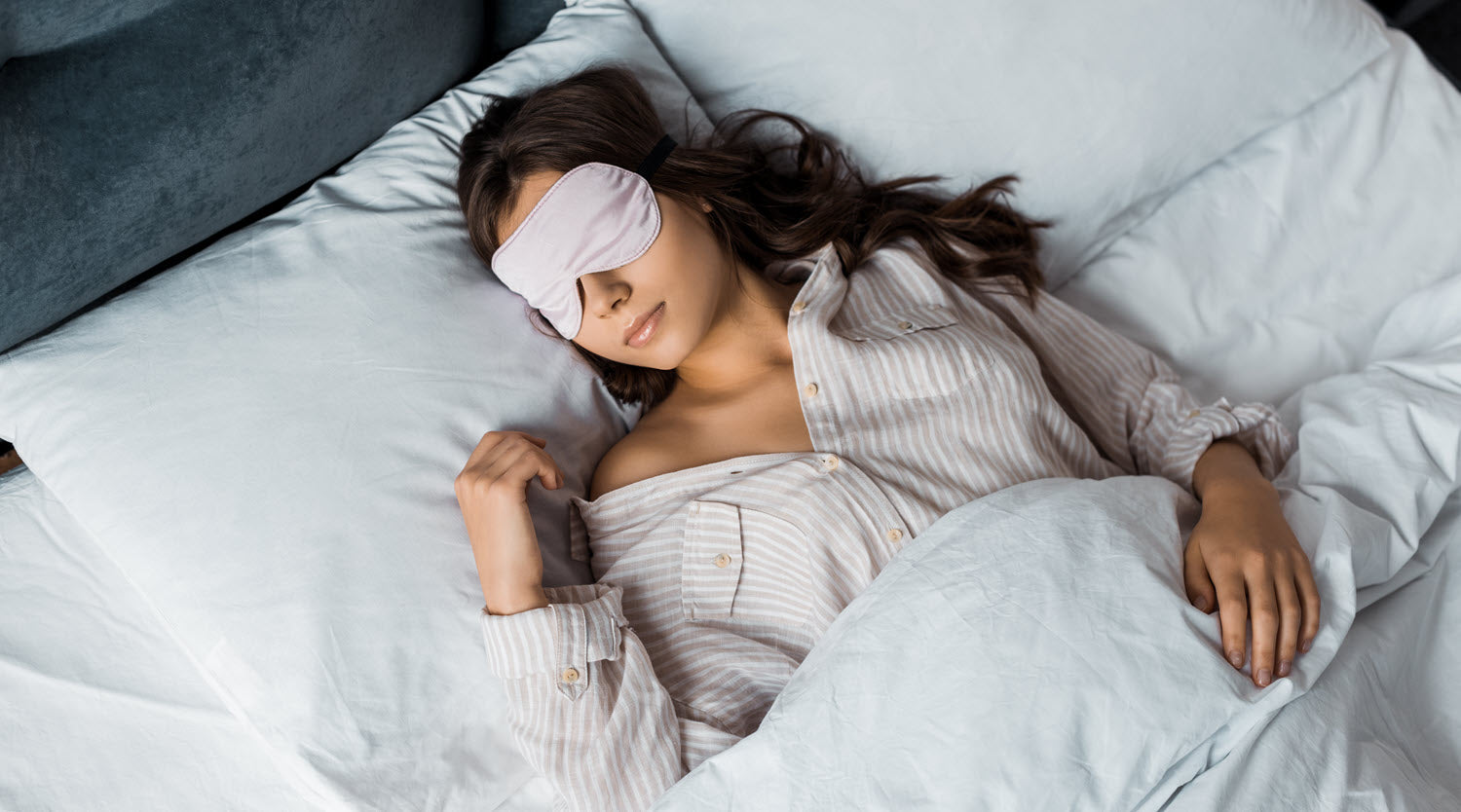 Woman using a Mulberry Park pure silk sleep mask in bed