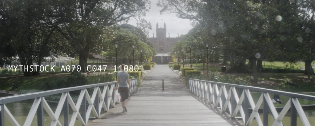 Pedestrian walks over footbridge toward Gothic building, day - hand-held shot