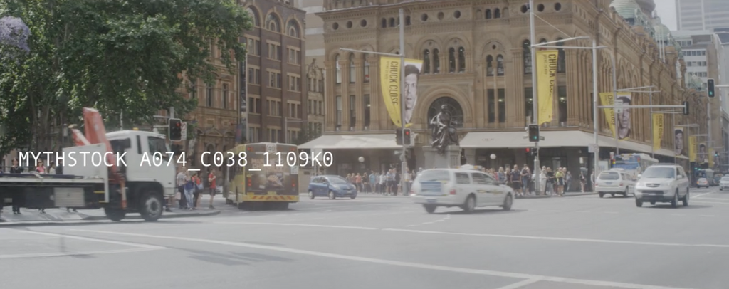 Pedestrians cross a four way intersection outside the QVB Sydney - hand-held shot