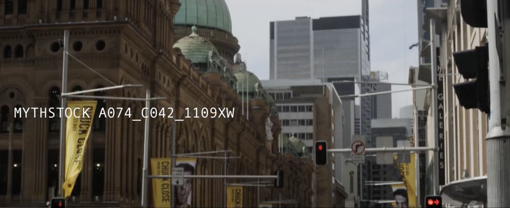 Traffic cycles past the Queen Victoria Building against modern skyline, establishing shot