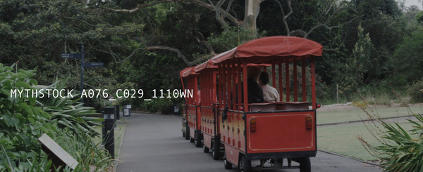 A small red tram drives through Sydney's Royal Botanic Gardens