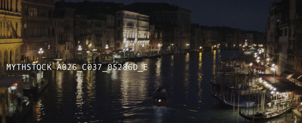 Following the boat through the Grand Canal at night from the Rialto Bridge