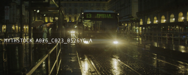 Stunning slow-motion shot of a bus slowing to a stop in the rain.