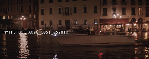 A boat courses down the Grand Canal at night, shimmering lights