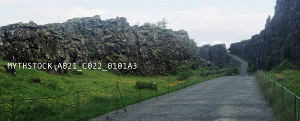 Jutting rock face next to a broad fenced off pathway in Iceland
