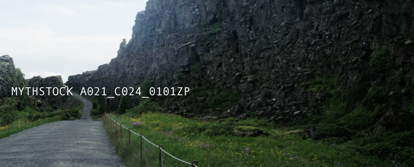 Black rocky cliff next to a winding pathway in Iceland