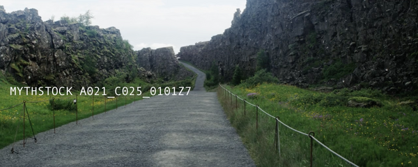 Black rocky cliff next to a broad winding pathway in Iceland