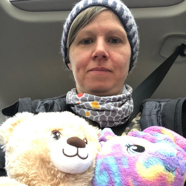 Isla sits with her niece and nephews stuffed toys in a car wearing a knit hat.