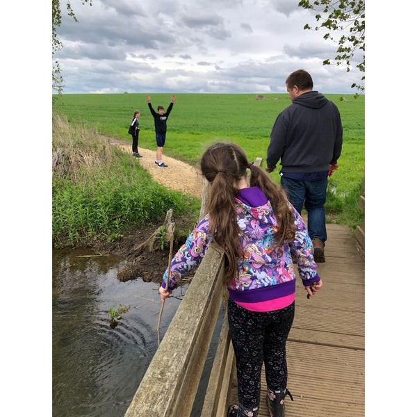 A girl standing on a bridge holding a stick over the side playing Pooh Sticks while her family walks ahead of her.