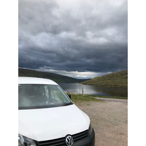 Tam the Van at the campsite with a sandy shore and water in the background.