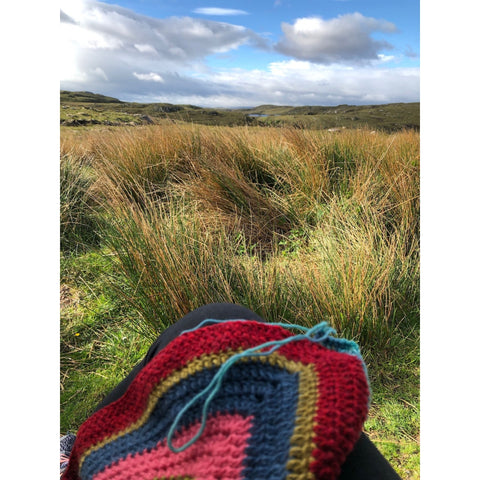 A crochet WIP among the long grasses and a bright cloudy day.