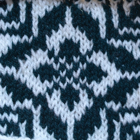 A colorwork swatch in green and white knit using Rauma Strikkegarn