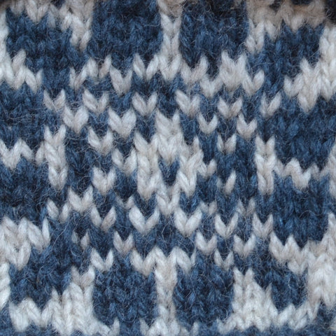 A colorwork swatch in blue and white knit using Rauma Vams
