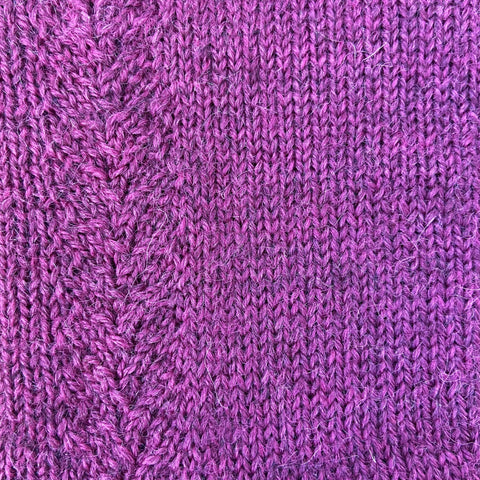 A closeup of a sock knit in John Arbon's Exmoor Sock Yarn in the Bell Heather color.