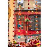 Strands of pompoms displayed in a shop window.