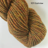 Skein of Harrisville Designs WATERshed worsted weight yarn in colorway 931, Eastview, a tweedy color with mustard tones in it.
