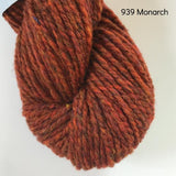 Skein of Harrisville Designs WATERshed worsted weight yarn in colorway 939, monarch, a tweedy red color.