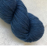 Skein of John Arbon Knit by Numbers DK  Merino Yarn in colorway 81, a shade of blue.