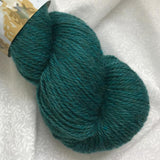 Skein of John Arbon Knit by Numbers DK  Merino Yarn in colorway 93, a shade of green.