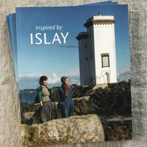 Cover of Inspired by Islay by Kate Davies, featuring two women standingon costal rocks with a lighthouse in the background. The women are wearing knit clothes and accessories.