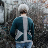 Back view of model wearing green knit sweater with geometric patterns.