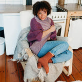 Woman curled up in chair wearing orange knit socks and a purple and white cardigan.