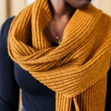 Model wearing a mustard yellow knit scarf.