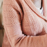 Model wearing pink textured knit sweater.