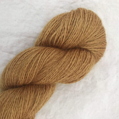 Skein of RiverKnits Wensleydale Wes 4ply wool yarn in colorway Polished Brass.