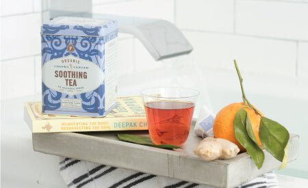 a clear cup of tea, fruit, and a box of tea bags on a tray