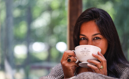 a woman drinking from a harney and sons tea cup