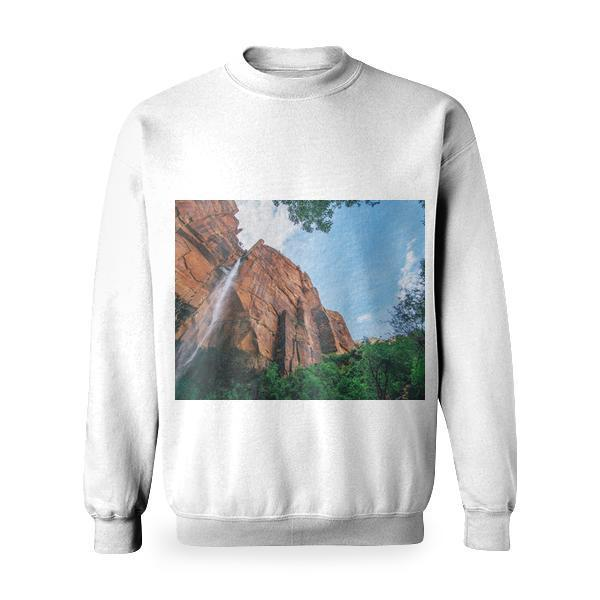 Waterfalls By Brown Rock Cliff Near Trees Under Blue Sky And White Clouds During Daytime Basic Sweatshirt